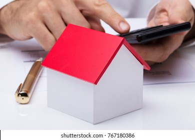 Close-up Of House Model With Person's Hand Using Calculator On Desk