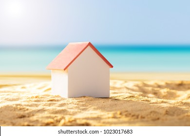 Close-up Of A House Model With Red Roof On Sandy Beach