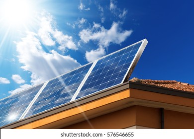 Close-up of a house roof with a solar panels on top, on a blue sky with clouds and sun rays