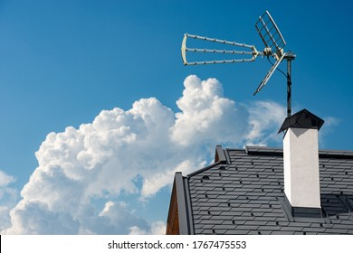 Closeup of a house roof with a television aerial, on a clear blue sky with clouds and copy space