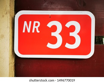 closeup of house sign number 33 numeral thirty three in vivid red with white text lettering
