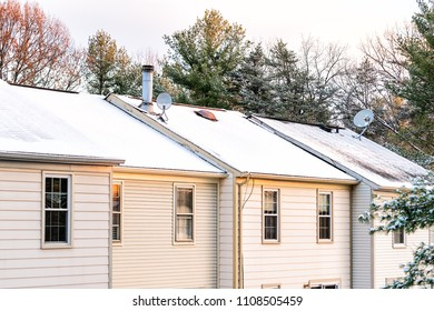 Closeup of house townhomes rowhouse rooftop roof with chimneys covered in white winter snow, cold season in Virginia