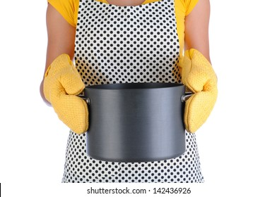 Closeup of a housewife wearing an apron holding a large pot in front of her body. Woman is not recognizable and wearing oven mitts. Vertical format isolated on white.