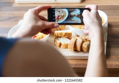 Closeup how womans hands photographing a vegetarian dish at health food restaurant