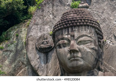 Closeup of a huge Japanese Great Buddha statue carved in stone, surrounded by green trees on a flat and green prairie, during the summer under intense sunlight.