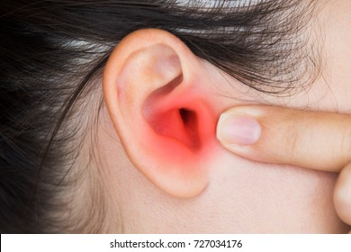 Closeup of a human ear with red painful area - Young woman has pain in the ear