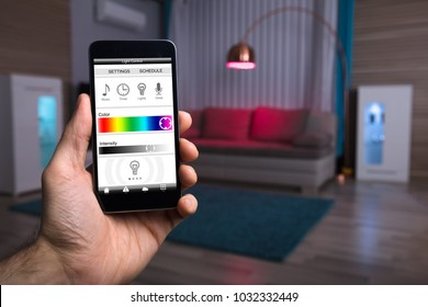 Close-up Of A Human Hand Adjusting Electric Light Through Mobile Phone At Home