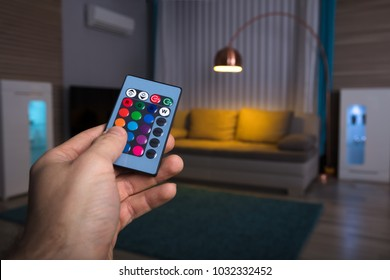 Close-up Of A Human Hand Adjusting Electric Light With Remote Control At Home