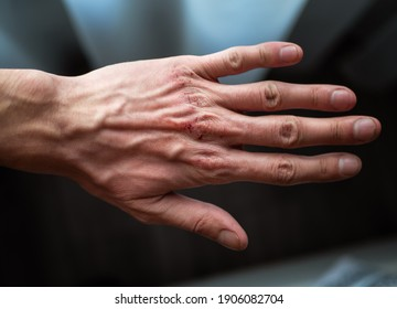 Close-up Of Human Hand Against Gray Background.