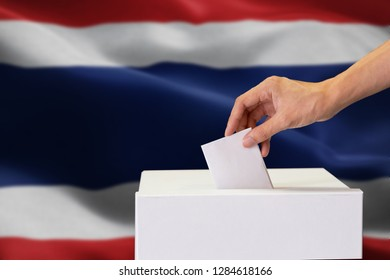 Close-up of human hand casting and inserting a vote and choosing and making a decision what he wants in polling box with Thailand flag blended in background