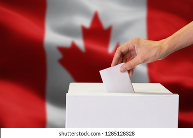 Close-up of human hand casting and inserting a vote and choosing and making a decision what he wants in polling box with Canada flag blended in background