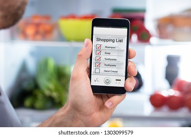 Close-up Of Human Hand Checking Shopping List On Mobilephone In Front Of Refrigerator