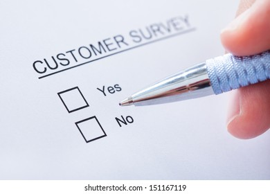 Close-up Of Human Hand Filling Customer Survey Form