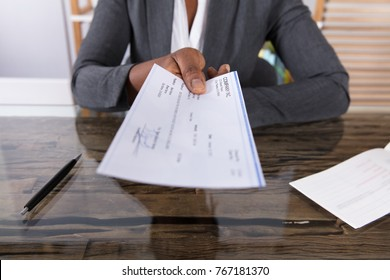 Close-up Of A Human Hand Giving Cheque On Desk