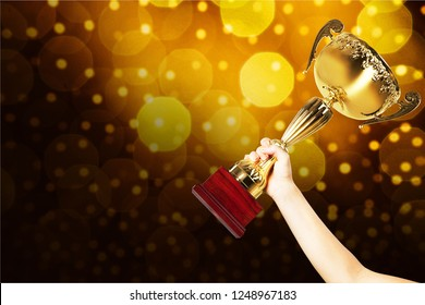 Close-up human hand holding golden Trophy on blurred  background
