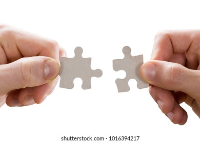 Close-up Of Human Hand Holding Jigsaw Puzzle On White Background