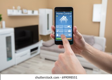 Close-up Of A Human Hand Holding Mobile Phone With Home Control System On Screen