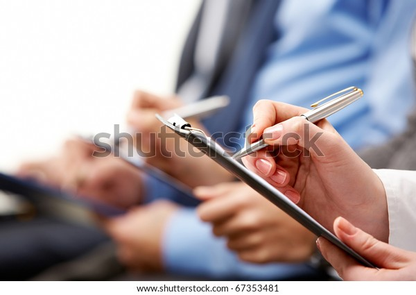 Close-up of human hand holding pen over business document