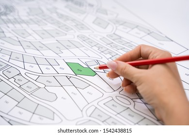 Close-up Of Human Hand Holding Pencil Over Paper Cadastre Map
