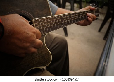 Closeup human hand playing guitar. Vintage style.
