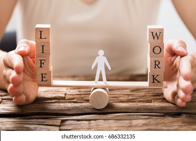 Close-up Of A Human Hand Protecting Balance Between Life And Work On Seesaw - Shutterstock ID 686332135