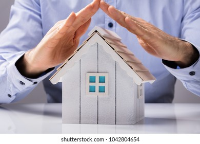 Close-up Of A Human Hand Protecting House Model On White Desk
