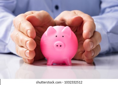 Close-up Of A Human Hand Protecting Pink Piggy Bank On White Desk