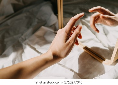 Close-up of human hand reflected in mirror, touching its own reflection.