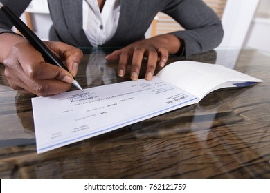 Close-up Of A Human Hand Signing Cheque On Desk