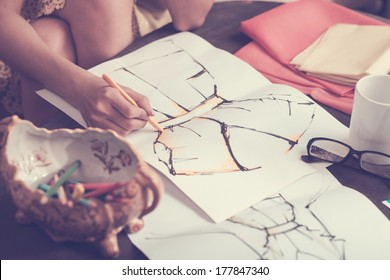 Closeup of a human hand sketching a dress for the new fashion collection on the foreground