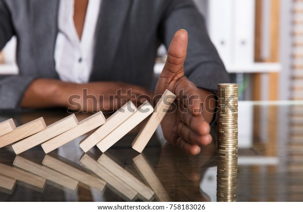 Close-up Of A Human Hand Stopping Wooden Blocks From Falling On Stacked Coins Over Desk