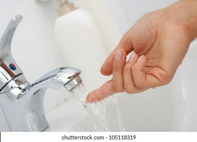 Close-up of human hand under stream of pure water from tap