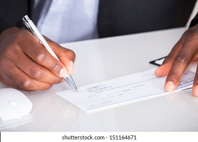 Close-up Of Human Hand Writing On Cheque
