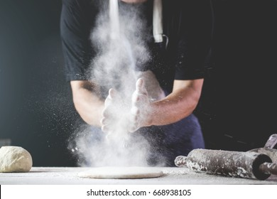 close-up of human hands in the apron knead the dough on a black wooden table, sprinkle with flour.Making dough by hands at bakery.