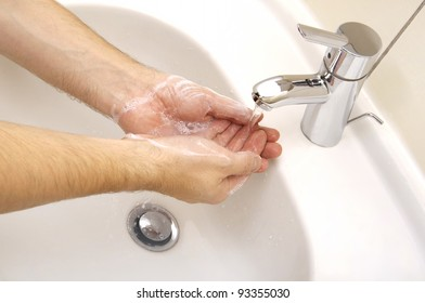 Close-up of human hands being washed under stream of pure water from tap