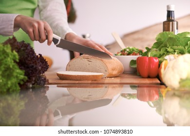 Closeup of human hands cooking in kitchen on the glass table with reflection Housewife slicing bread