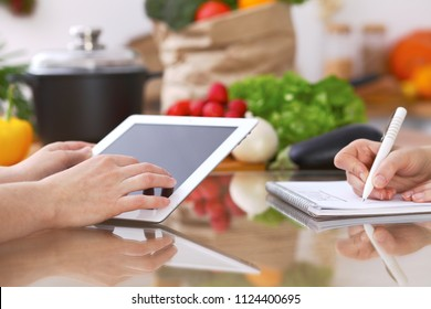 Closeup of human hands cooking in kitchen using touch pad. Women discuss a menu. Healthy meal, vegetarian food and lifestyle concept