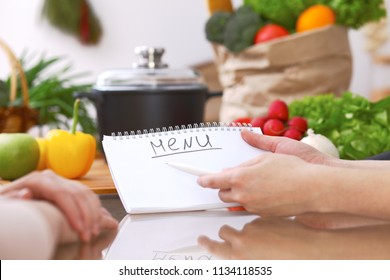 Closeup of human hands cooking in kitchen. Women discuss a menu. Healthy meal, vegetarian food and lifestyle concept