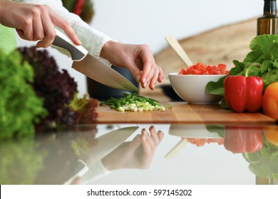 Closeup of human hands cooking vegetables salad in kitchen on the glass table with reflection. Healthy meal and vegetarian concept