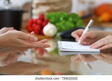 Close-up of human hands are gesticulate over a table in the kitchen. Women choosing menu or making online shopping. So much ideas for tasty cooking
