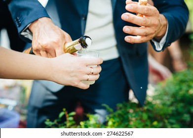 Close-up of human hands holding glasses of champagne.