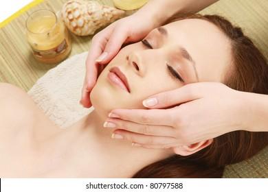 Closeup of human hands massaging a young pretty woman's face