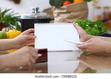 Close-up of human hands pointing into note book copy space area in the kitchen.  So much ideas for tasty cooking. Vegetarian, healthy meal and friendship concept