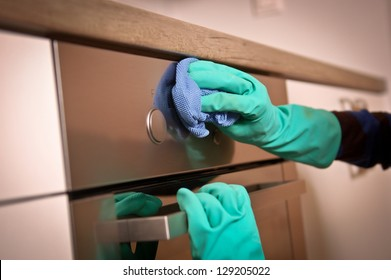Close-up of human hands polishing the oven