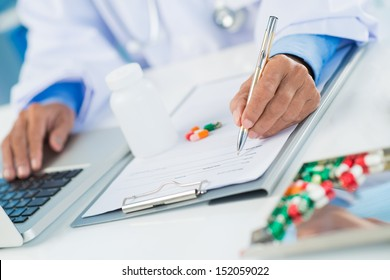 Close-up of human hands prescribing medicaments on the foreground