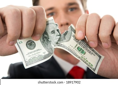 Close-up of human hands tearing hundred-dollar banknote