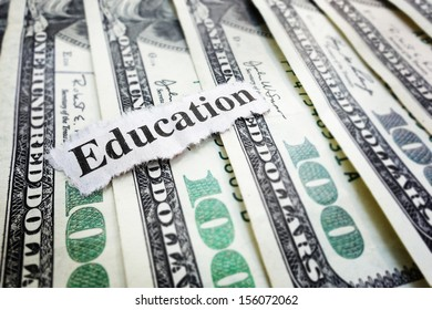 "Closeup of hundred dollar bills and ""Education"" news headline"