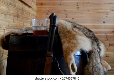 Closeup of a hunters gun with whiskey and an animal pelt.