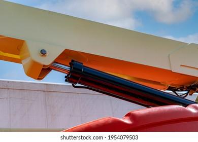 Closeup hydraulic of boom lift. Orange articulated boom lift. Maintenance and repair hydraulic boom lift service. Aerial platform. Telescopic boom lift. Mobile construction crane. Hydraulic cylinder. - Shutterstock ID 1954079503