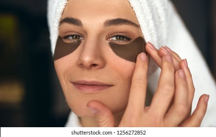 Closeup iamge of beautiful woman after bath with towel on head puts patches under the eyes from wrinkles and dark circles. Attractive female smiling and making beauty treatments on the face at home
